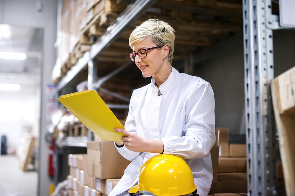 Donna che guarda una cartelletta in un magazzino