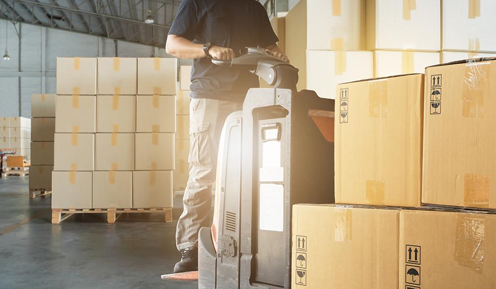 Ragazzo che sposta scatoloni con muletto