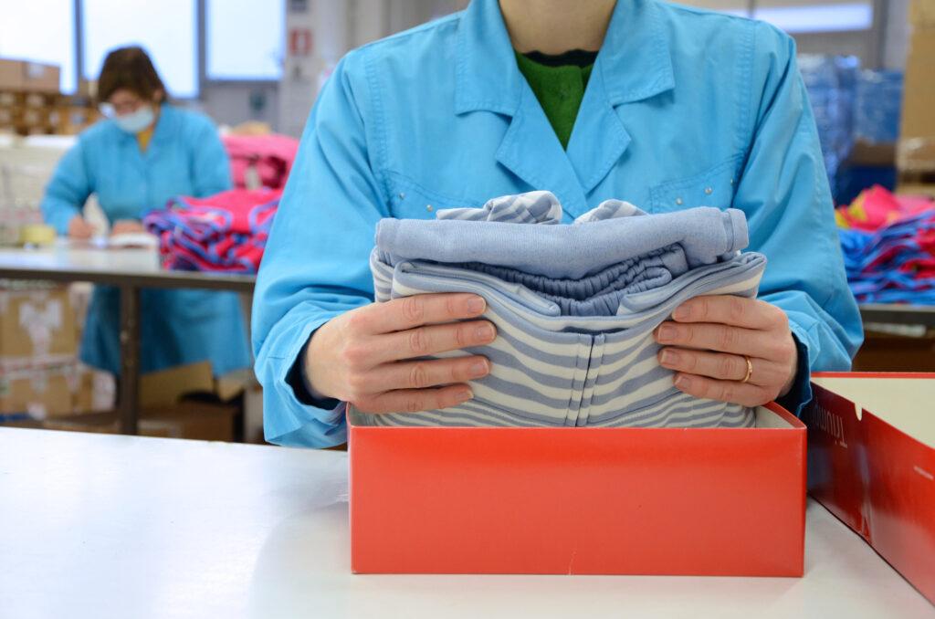 Addetta che inserisce un pigiama in una scatola
